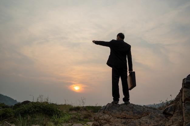 Uomo d'affari in piedi sulla montagna a sfondo tramonto, concetto di successo aziendale.