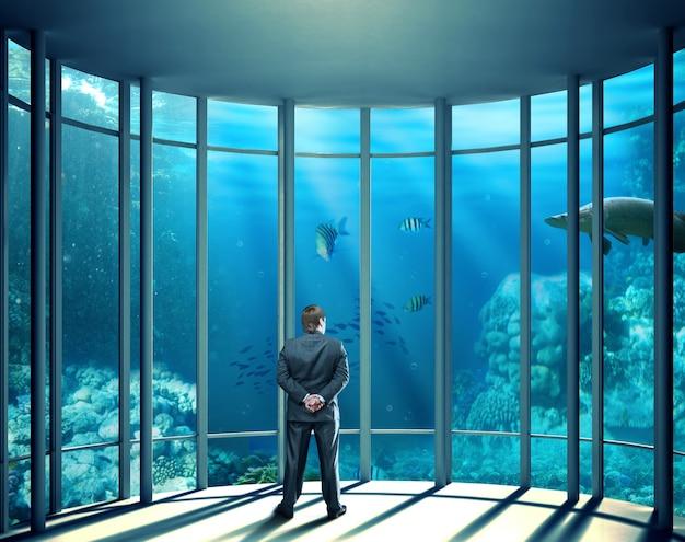 Uomo d'affari in piedi in ufficio e guardando la vita marina sott'acqua