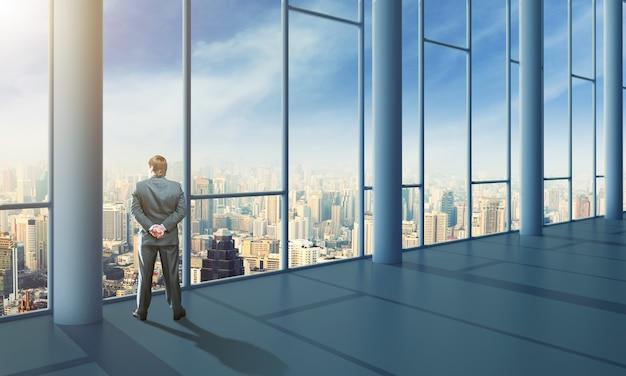 Uomo d'affari in piedi in ufficio e guardando il cielo