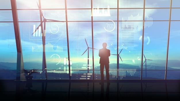 Un uomo d'affari in piedi di fronte a dati infografici virtuali e finestra panoramica del suo grande ufficio sullo sfondo di un parco eolico