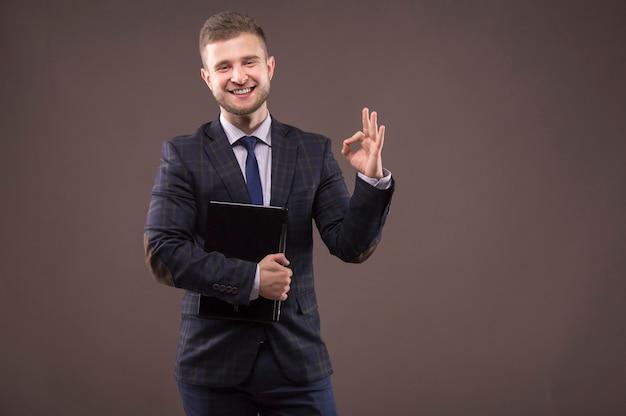 Uomo d'affari in piedi in tuta con il computer portatile nelle sue mani e che mostra segni di ok