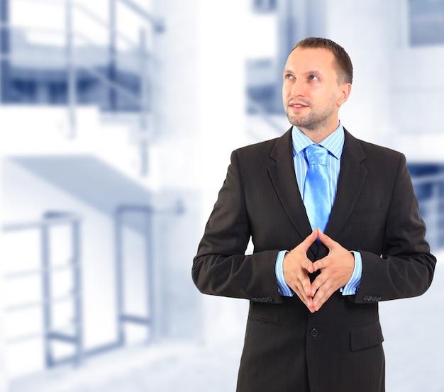 Uomo d'affari in piedi su sfondo bianco, guardando in lontananza