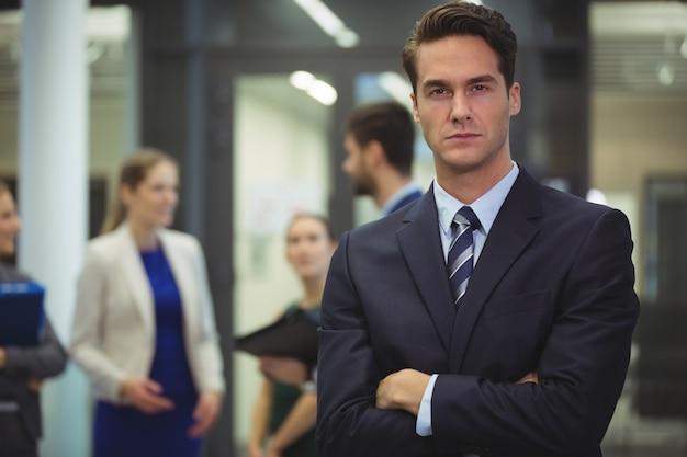 Uomo d'affari in piedi con le braccia incrociate in ufficio