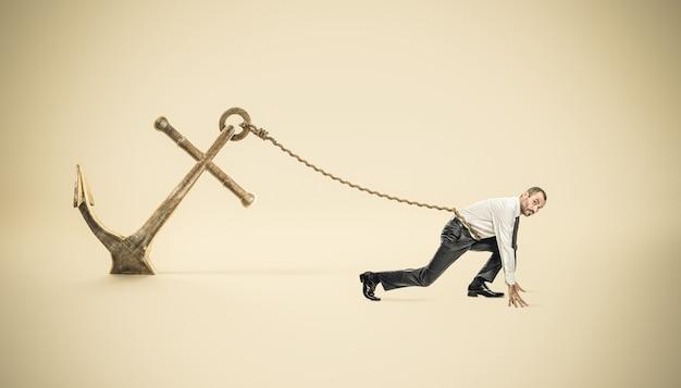 Uomo d'affari in posizione di partenza legato ad una grossa ancora fissata a terra.