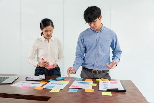 Imprenditore attaccare note colorate al brainstorming sul tavolo lavorando su un nuovo progetto per condividere l'idea di pensare a come pianificare un nuovo caso.