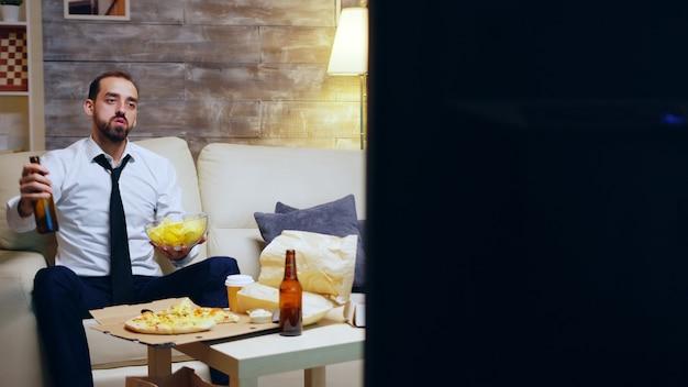 Uomo d'affari ancora nel suo vestito seduto sul divano tifo mentre guarda lo sport in tv. imprenditore in possesso di chip.