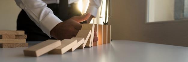 Uomo d'affari che ferma l'effetto domino inserendo la mano in una linea di blocchi che cadono con uno sprazzo di sole luminoso da dietro