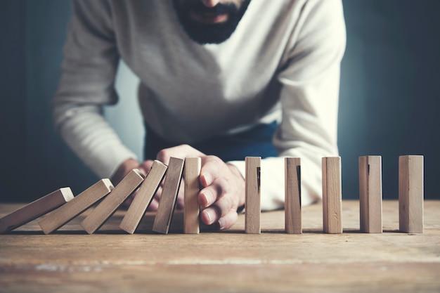 Uomo d'affari che ferma l'effetto domino