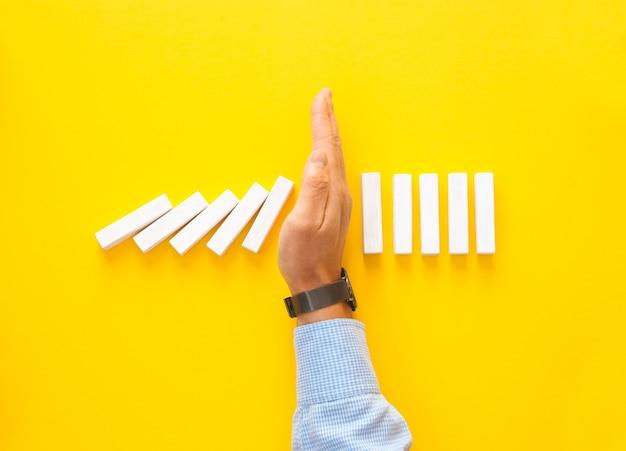Uomo d'affari fermare la caduta di pezzi del domino sulla superficie gialla