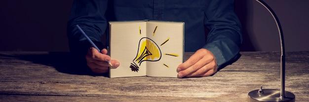 Uomo d'affari o studente che mostra il suo taccuino funzionante con una lampadina disegnata a mano