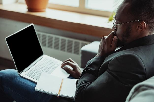 Uomo d'affari o studente che lavora da casa è isolato o mantiene la quarantena a causa del coronavirus. uomo afroamericano che utilizza laptop, tablet e cuffie. conferenza online, lezione, ufficio remoto.