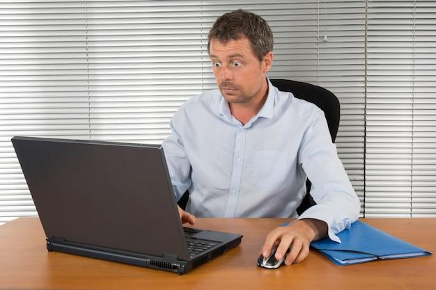 Uomo d'affari sbalordito e stupito fissando il suo computer portatile