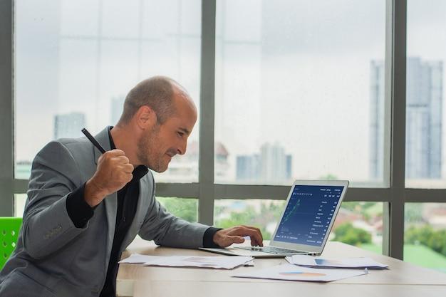 Successo dell'uomo d'affari che commercia online con la crescita del mercato del grafico digitale, commerciante felice nel commercio di profitto
