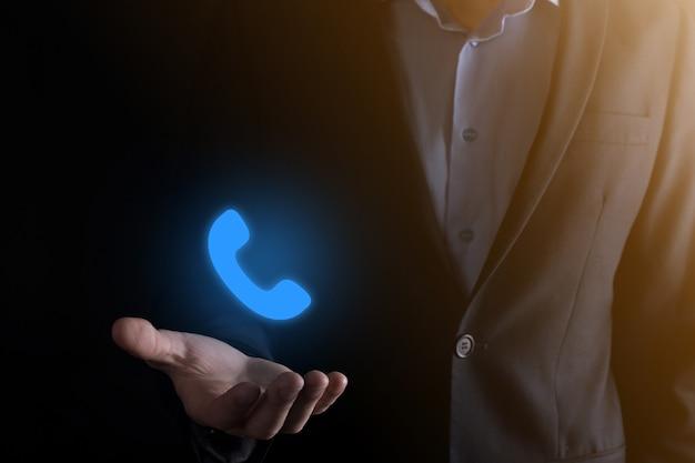 Imprenditore in tuta su sfondo nero tenere premuto il telefono icon.call now business communication support center customer service technology concept.