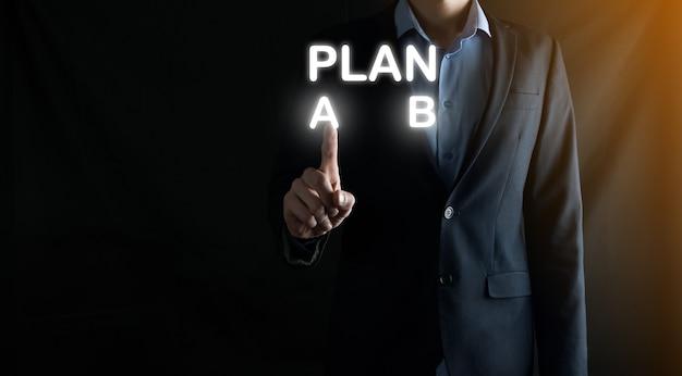 L'uomo d'affari in un vestito sceglie le opzioni per lo sviluppo del piano