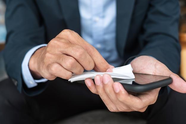 Uomo d'affari in tuta che pulisce lo smartphone con salviettine umidificate e disinfettante con alcol in ufficio o in un bar, infezione da coronavirus (covid-19) di protezione. superficie pulita e concetto new normal