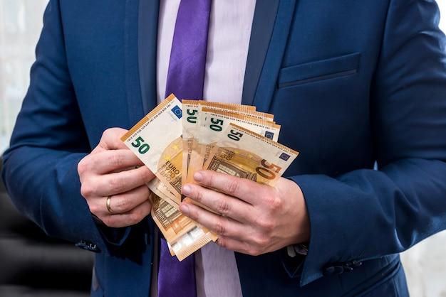 Uomo d'affari in vestito che conta le banconote in euro, primo piano
