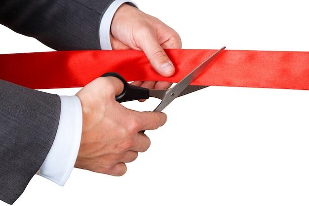 Uomo d'affari in vestito che taglia il nastro rosso con un paio di forbici