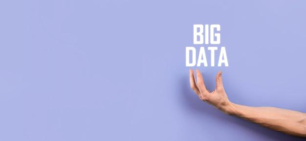 L'uomo d'affari in un vestito su uno sfondo scuro tiene la scritta big data. concetto di server online di rete di archiviazione. rappresentazione di social network o analisi aziendale