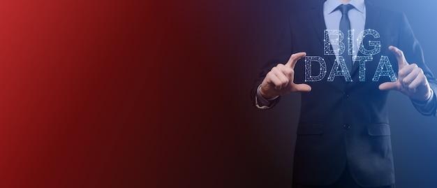 Uomo d'affari in un vestito su uno sfondo scuro detiene la scritta big data. concetto di server online di rete di archiviazione rappresentazione di social network o analisi aziendale.