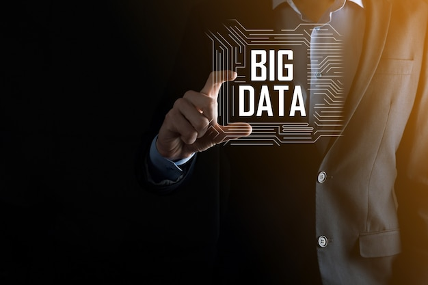 L'uomo d'affari in un vestito su uno sfondo scuro tiene la scritta big data. rete di archiviazione online