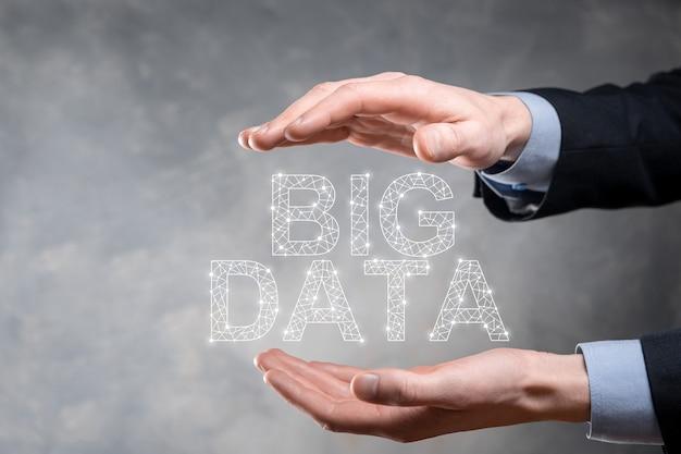 Uomo d'affari in un vestito su uno sfondo scuro detiene la scritta big data.