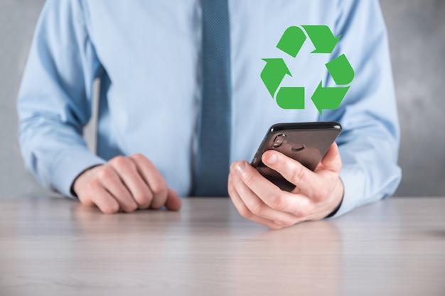 Uomo d'affari in tuta su sfondo scuro tiene un'icona di riciclaggio, segno nelle sue mani. ecologia, ambiente e concetto di conservazione. luce al neon rosso blu.