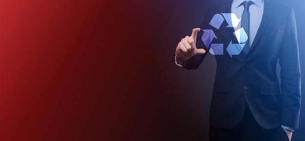 Uomo d'affari in tuta sulla superficie scura detiene un'icona di riciclaggio, segno nelle sue mani