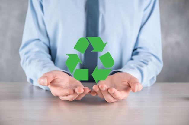 Imprenditore in tuta sulla superficie scura detiene un'icona di riciclaggio, segno nelle sue mani