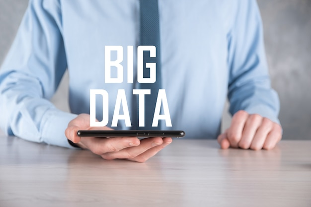 L'uomo d'affari in un vestito su un muro scuro detiene la scritta big data. concetto di server online di rete di archiviazione rappresentazione di social network o analisi aziendale.