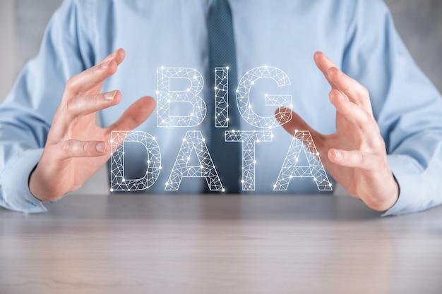 L'uomo d'affari in un vestito su una parete scura tiene la scritta big data. concetto di server online di rete di archiviazione. rappresentazione di social network o analisi aziendale.