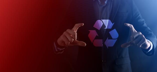 L'uomo d'affari in vestito sopra la parete scura tiene un'icona di riciclaggio, firma nelle sue mani. ecologia, ambiente e concetto di conservazione. luce al neon rosso blu.