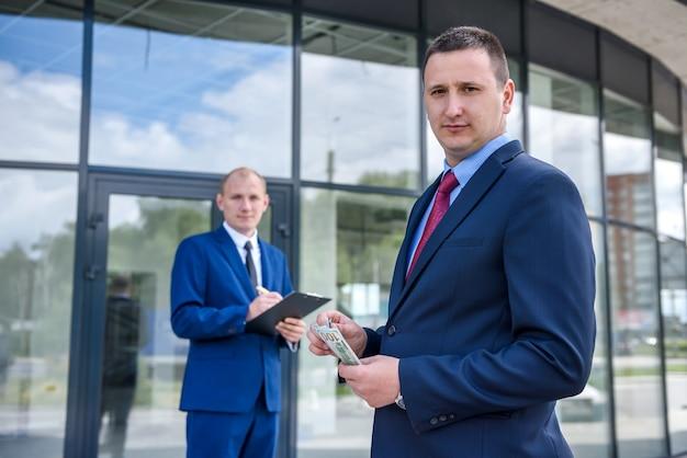 Uomo d'affari in vestito che dà le banconote del dollaro ad un altro