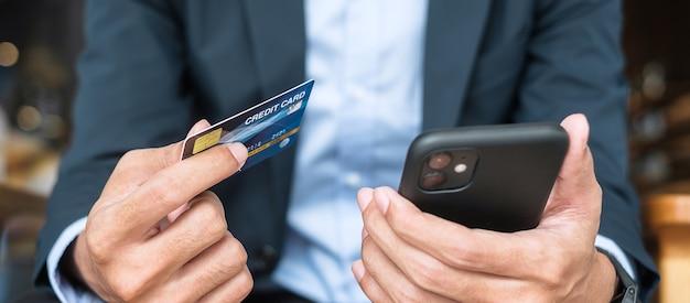 Uomo d'affari in tuta con carta di credito e utilizzo di smartphone touchscreen per lo shopping online mentre effettua ordini al bar o in ufficio. business, tecnologia, e-commerce e concetto di pagamento online