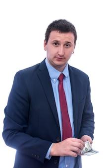 Uomo d'affari in vestito che tiene il pacco del dollaro nelle mani isolate sul muro bianco