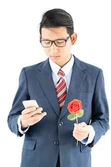 Uomo d'affari in vestito che tiene smartphone e rosa rossa