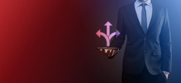L'uomo d'affari in giacca e cravatta tiene un cartello che mostra tre direzioni. nel dubbio, dovendo scegliere tra tre diverse scelte indicate da frecce che puntano in senso opposto concetto. tre modi per scegliere
