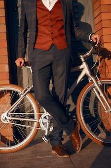Uomo d'affari in vestito che si appoggia sulla bicicletta