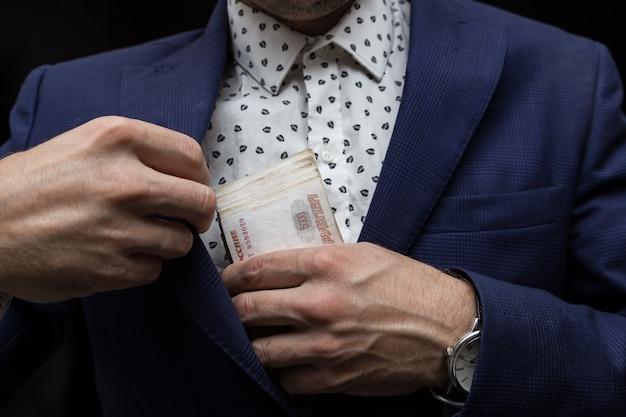 Un uomo d'affari in giacca e cravatta mette in tasca un pacco di soldi russi il concetto di corruzione