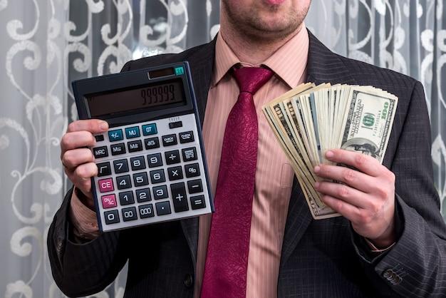 Uomo d'affari in vestito che mostra banconote in dollari e calcolatrice