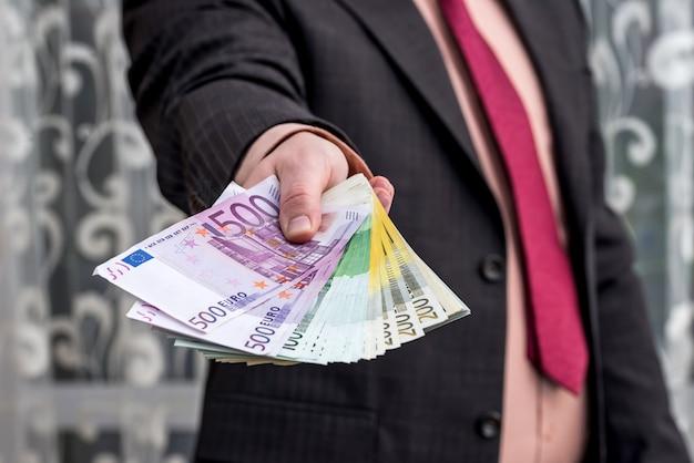 Uomo d'affari in tuta che mostra e offre banconote in euro e dollari