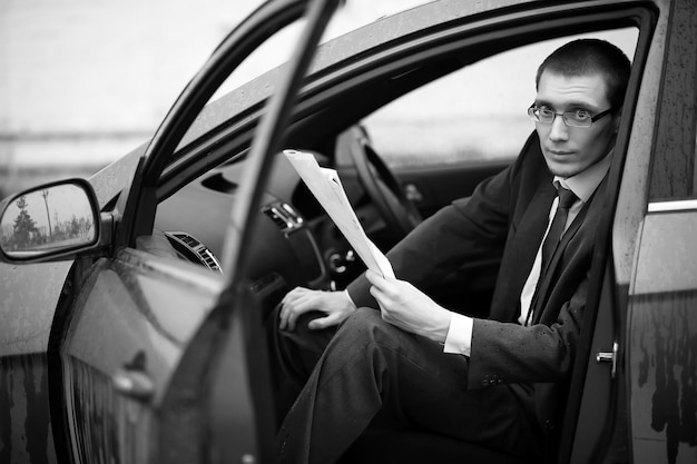 Uomo d'affari in giacca e cravatta per strada in macchina
