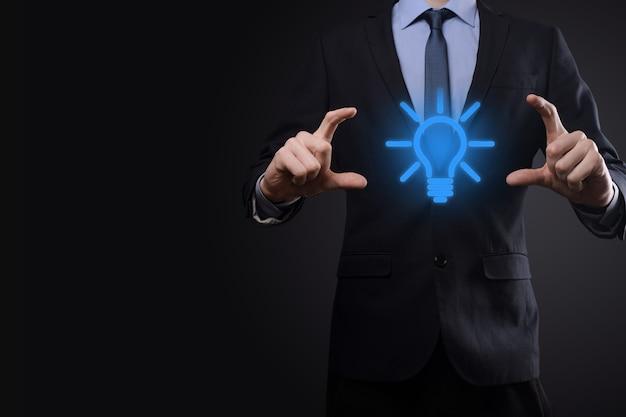 Uomo d'affari in un vestito con una lampadina nelle sue mani. tiene in mano un'icona di un'idea brillante. con un posto per il testo.