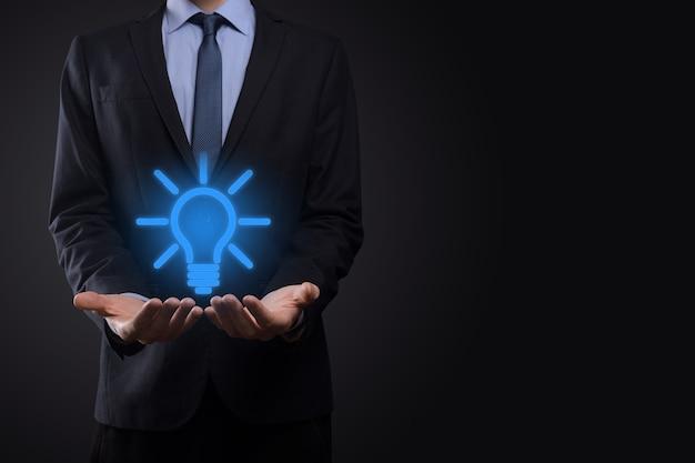 Uomo d'affari in un vestito con una lampadina nelle sue mani. tiene in mano un'icona di un'idea brillante