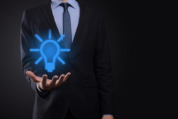 Uomo d'affari in un vestito con una lampadina nelle sue mani