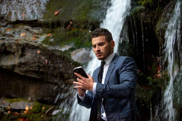 Uomo d'affari in tuta con smartphone sullo sfondo della cascata. concetto di dispositivo impermeabile. uomo d'affari di telelavoro con telefono ip68.