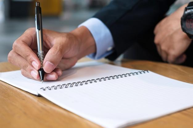 Uomo d'affari in tuta che scrive qualcosa sul taccuino in ufficio o al bar, mano dell'uomo che tiene la penna con la firma sul rapporto cartaceo. concetti di business