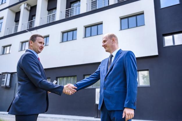 L'uomo d'affari in giacca e cravatta fa un accordo con le banconote in euro