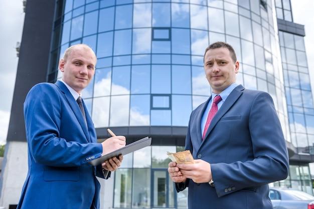L'uomo d'affari in giacca e cravatta fa affare con le banconote in euro