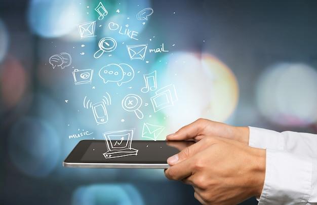Uomo d'affari e tablet pc con schizzi astratti di icone di affari sullo sfondo
